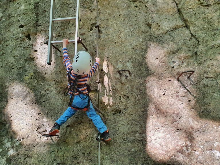 Ein fünfjähriges Kind auf einem Klettersteig. Es versucht auf eine Leiter zu klettern.