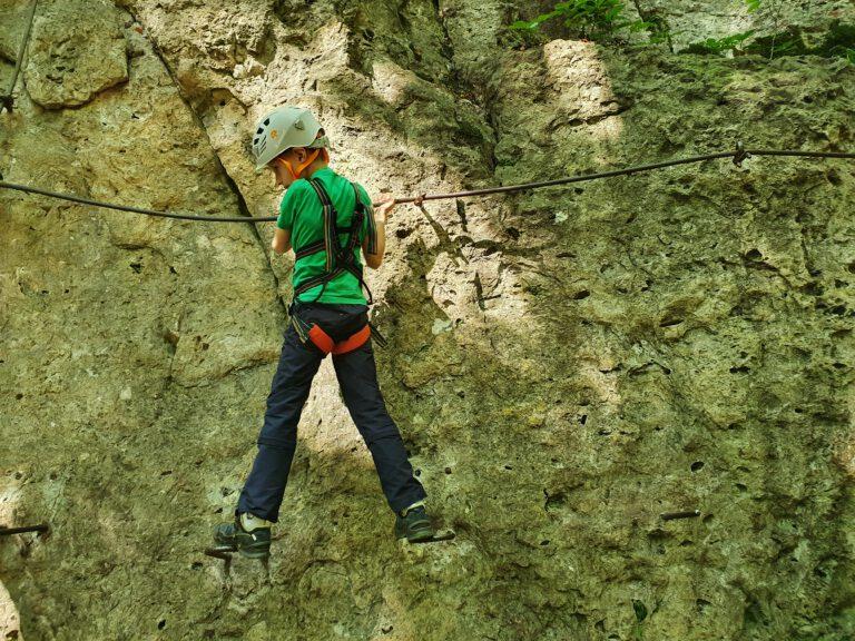 Ein sieben jähriges Kind konzentriert auf einem Klettersteig.