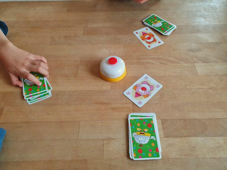 Bunte Karten mit Clownsmotiven und einer Klingel in der Mitte auf einem Tisch.