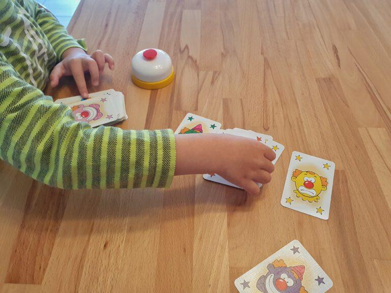Eine Kinderhand die bunte Karten sortiert.