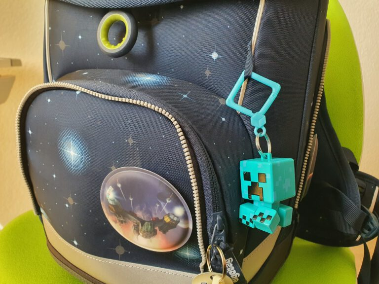 Ein blauer Schulrucksack mit Sternen drauf und einem Creeper-Anhänger.