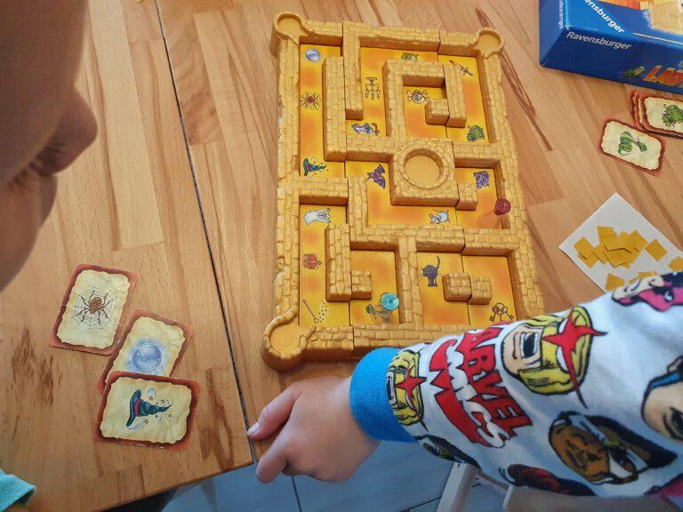 Zwei Kinder die ein Brettspiel spielen das aussieht wie ein Labyrinth. Auf dem Tisch liegen Karten mit verschiedenen Symbolen.