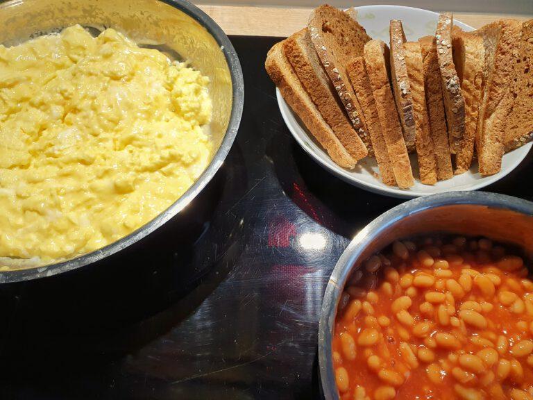 Eien Pfanne mit Rührei. Ein Teller mit Brot und Toast. Ein Topf mit gebackenen Bohnen.