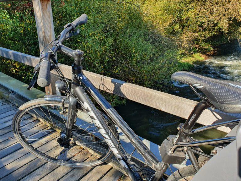 Ein schwarzes Fahrrad auf einer Holzbrücke.