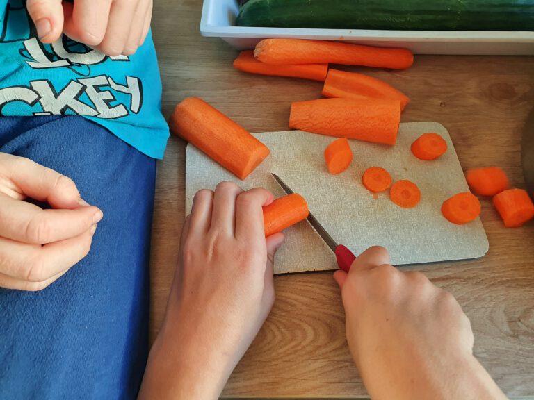 4 Kinderhände. 2 davon schneiden eine Möhre. Die anderen beiden Hände sammeln das Gemüse ein.