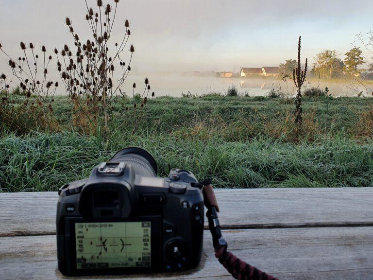 Eine schwarze Kamera auf einer gefroren Holzbank, die auf einen nebeligen Weiher ausgerichtet ist.