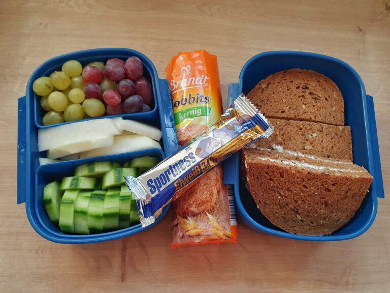 2 blaue Boxen mit Essen. In der linken sind grüne und rote Weintrauben, Kohlrabi, und Gurken. Rechts sind Brote und in der Mitte eine Packung Kekse und Eiweißriegel.