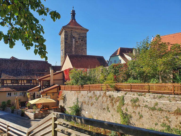 Im Vordergrund ist eine alte Burgmauer. Im Hintergrund sieht man einen großen Turm. Der Himmel ist wolkenlos blau.